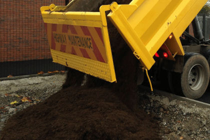a tipper lorry delivering top soil to site